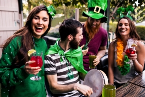 people in green clothes and green leprechaun hats holding drinks